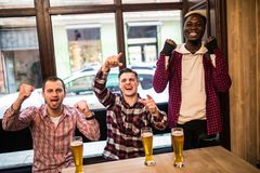 Watching TV in pub. Happy multiracial young friends are cheering for team and smiling while spending time together in pub. royalty free stock photography