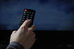 Watching TV with remote control Stock Image
