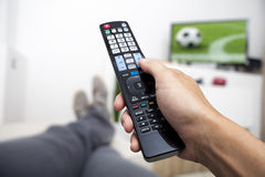 Watching TV. Remote control in hand. Football. Watching football on TV. Remote control in hand. Man lying on the couch watching TV stock photo