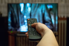 Watching tv and using remote control Royalty Free Stock Photo