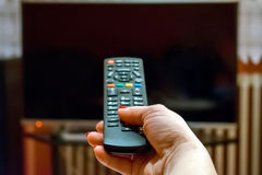 Watching tv and using remote control Royalty Free Stock Photos