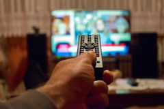 Watching tv and using remote control Stock Photos