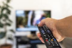 Watching tv and using remote control stock image