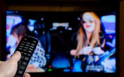 Watching TV and using remote controller.  stock photos