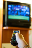 Watching TV and using remote controller Royalty Free Stock Photography