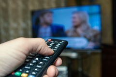 Watching TV and using remote controller. Hand holding remote control in front and operating TV on background Royalty Free Stock Images