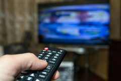 Watching TV and using remote controller Stock Photography