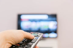 Watching TV and using remote controller. Hand holding TV remote control with a television in the background. Smart tv Stock Photography