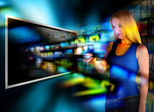Watching Video TV with Remote Control. A person is holding a remote control and watching television on a widescreen tv with video images coming out on a black Royalty Free Stock Photography
