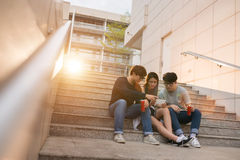 Watching videos. Students sitting on the steps and watching video on smartphone Royalty Free Stock Image