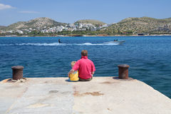 Watching a Waterskier. Father and Son sitting on a pier watching a waterskier stock image
