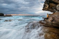 Watching the waves rush by, just like life from sea cave Stock Photography