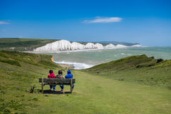 Three people sitting on a bench on a sunny day watching the waves Royalty Free Stock Images