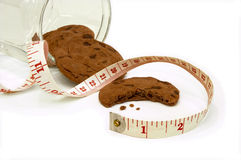 Watching What You Eat. Some chocolate-chip cookies spilt out of a glass jar with a measuring tape next to them. One cookie has had a bite taken out of it royalty free stock image