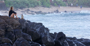 Watching the winter swells. HOOKIPA, HAWAII - DECEMBER 1, 2015: Female surfer overlooking the water at Hookipa, Maui. Hookipa is a beach on the north shore of Royalty Free Stock Image