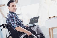 Joyful brunette posing on camera. Watching you. Attractive young man turning head while keeping laptop on knees Stock Photography
