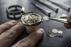 Watchmaker επισκευάζει τα μηχανικά ρολόγια στο εργαστήριό του στοκ φωτογραφία