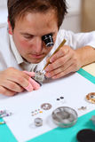Watchmaker. In his workshop repairing a wrist watch. Intentional shallow depth of field Royalty Free Stock Images