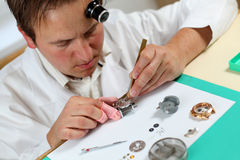 Watchmaker. In his workshop repairing a wrist watch. Intentional shallow depth of field Stock Images