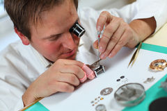 Watchmaker. In his workshop repairing a wrist watch. Intentional shallow depth of field, focus on the eye Stock Photos