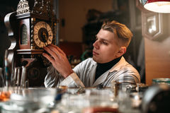 Watchmaker adjusts the mechanism of old wall clock Royalty Free Stock Photography