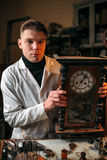 Watchmaker adjusts the mechanism of old wall clock. In the workshop stock photo