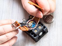 Watchmaker changes battery in quartz wristwatch. Watch repairer workshop - watchmaker changes battery in quartz wristwatch with plastic tweezers on wooden table stock photo