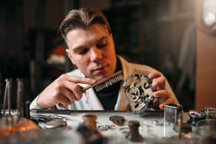 Watchmaker cleans the mechanism of old watches Stock Photos