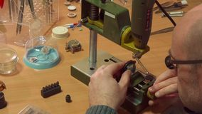 Watchmaker customizes drill press. Hairless watchmaker customizing drill press at the workshop. Caucasian man change the height of entire drill head. Middle aged Royalty Free Stock Photography