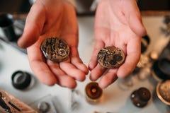 Watchmaker hands with clockwork mechanism closeup Royalty Free Stock Photo