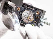 Watchmaker in head-mounted magnifier repairs watch. Watchmaker workshop - watchmaker in head-mounted magnifier repairs old watch with screwdriver Stock Photo