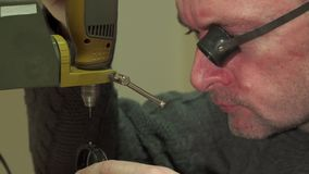 Watchmaker makes perforation in some watch piece. Middle aged watchmaker making perforation in some watch piece. Bald repairer fixing part on drill press. Close Stock Image