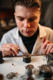 Watchmaker repair broken clockwork with tweezers Stock Photos