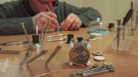 Watchmaker repaires repeater. Middle aged male watchmaker repairing repeater. Close up of tools and watch pieces on the table. Camera tilting up along repairer Stock Photography