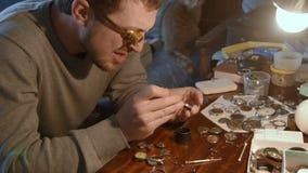 Watchmaker repairing clockwork. Watchmaker clockwork repairs in the workshop stock footage