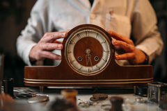 Watchmaker restore old wooden table clock Royalty Free Stock Photos