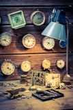 Watchmaker`s workshop with clocks, spare parts and tools. On wooden table royalty free stock image