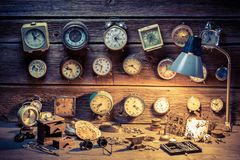 Watchmaker`s workshop with many clocks, tools and spare parts. On wooden table stock photos