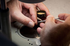 Watchmaker screwing a screw on a balancewheel. Close-up on the hands of a watchmaker holding a little box full of screws and a balanccewheel with the left hand Stock Image