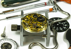 Watchmaker table. Open clock machine and several horology tools Royalty Free Stock Photo