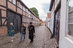 Watchman in old narrow street in Ribe, Denmark. Watchman in old narrow street with cobblestones and old houses in Ribe, Denmark guiding tourists around Royalty Free Stock Images
