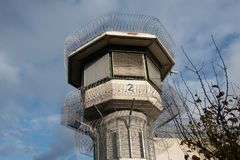 Watchtower of a correctional facility of a prison with a balustrade and two rows of barbed wire rolls in front of a dramatic sky stock photos