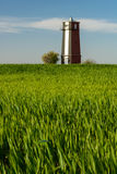 Watchtower on the field. Against the sky and green grass with trees Royalty Free Stock Photos