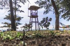 Watchtower kant van strand met boom en duidelijke hemel stock afbeelding