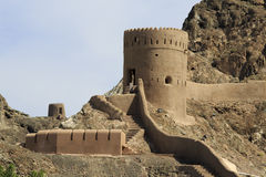 Watchtower with steps and mountains in Old Muscat royalty free stock image