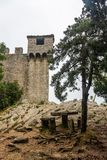 Watchtower on the wall surrounding Guaita Fortress in San Marino in the fog royalty free stock images