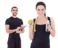 健身辅导员和年轻美丽的妇女有瓶的wate 免版税库存图片