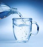 Water. Clear blue water being poured into a glass mug. Photos in blue tone Royalty Free Stock Photos