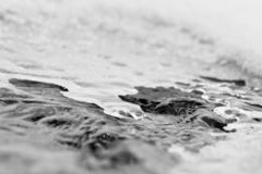 Water. The end of a season: the water of a river running under the melting ice Royalty Free Stock Image