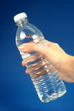 Water. Hand holding a water bottle against a blue background Stock Photo